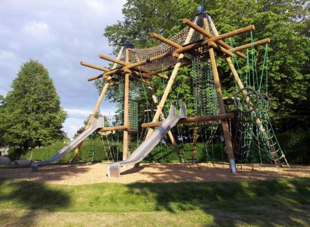Large timber and rope climbing frame with metal slides in park