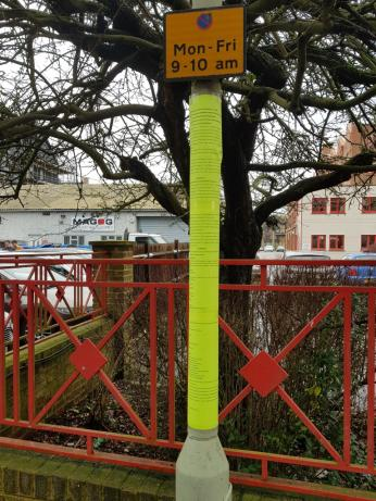 Parking restriction sign post covered in florescent yellow tape