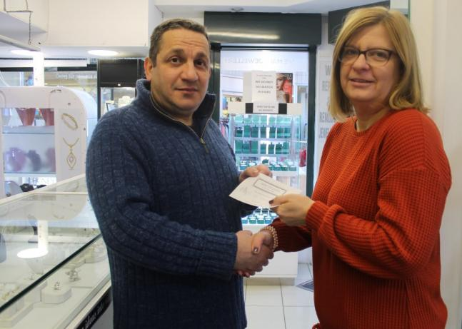 Jewel of Hearts owner handing over lottery win to bride to be Deborah Rogers inside shop