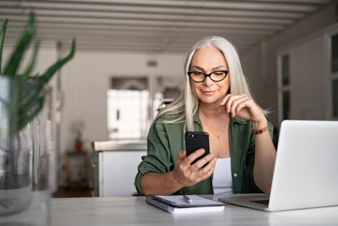 woman looking at mobile phone working in home office