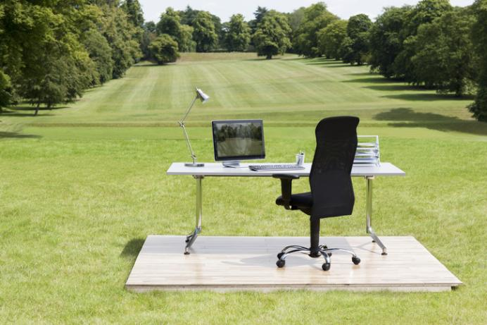 Office desk and chair superimposed outside in open field landscape