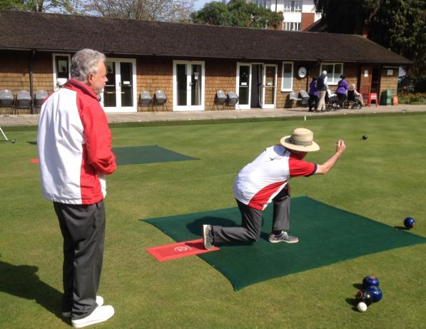Two men playing bowls at bowls club