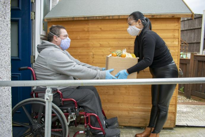 lady with a food produce delivery to the front door of a male in a wheelchair. Both people wearing face coverings.