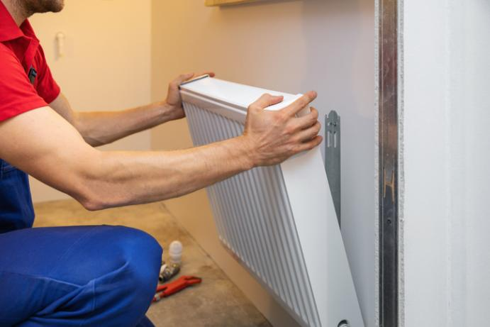 workman's hands installing radiator to wall