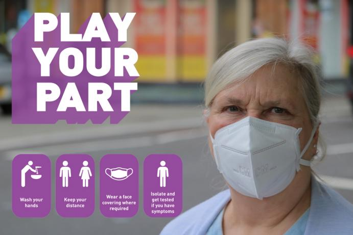 Cllr wearing a face covering with 'Play your Part' logo in purple