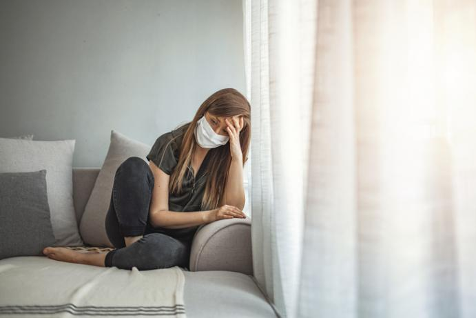 Depressed young woman sitting on couch, wearing face mask, head drooping