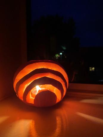 strips carved out of a pumpkin with candlelight showing through