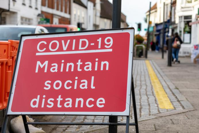 Red road sign with COVID-19 maintain social distance text in white