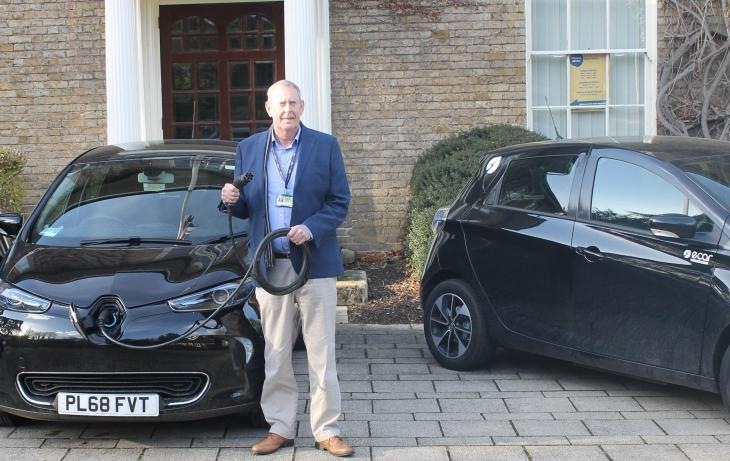 Man standing with an electric car holding the cable coming from the front of the car