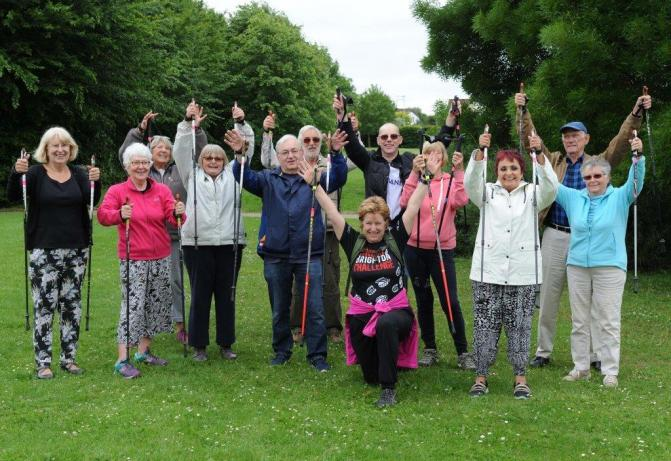 Nordic walking group in park holding up walking sticks
