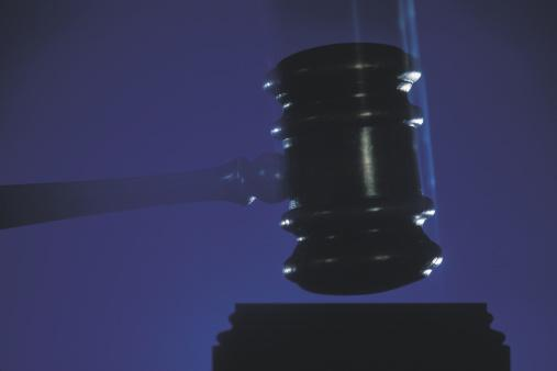picture of a gavel being slammed down with dark background