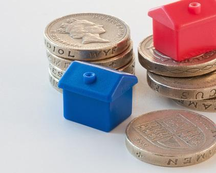 little plastic monopoly type houses with stacks of pound coins