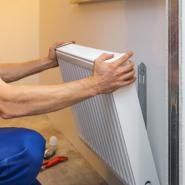 workman's hands installing radiator to wall