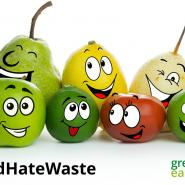 Different types of coloured fruit with smiling faces on a white background and with Love Food Hate Waste hashtag in black writing and Greener East Herts and East Herts Council logos