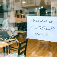 A shop window with a sign that says Temporarily Closed Covid-19