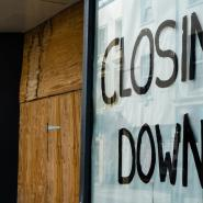Shop front with closed down sign and door boarded up